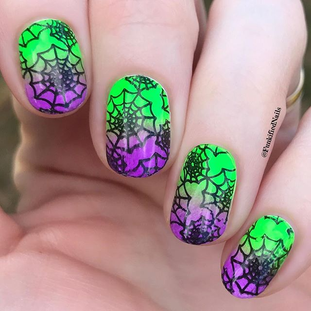 green and purple spider web design on nails