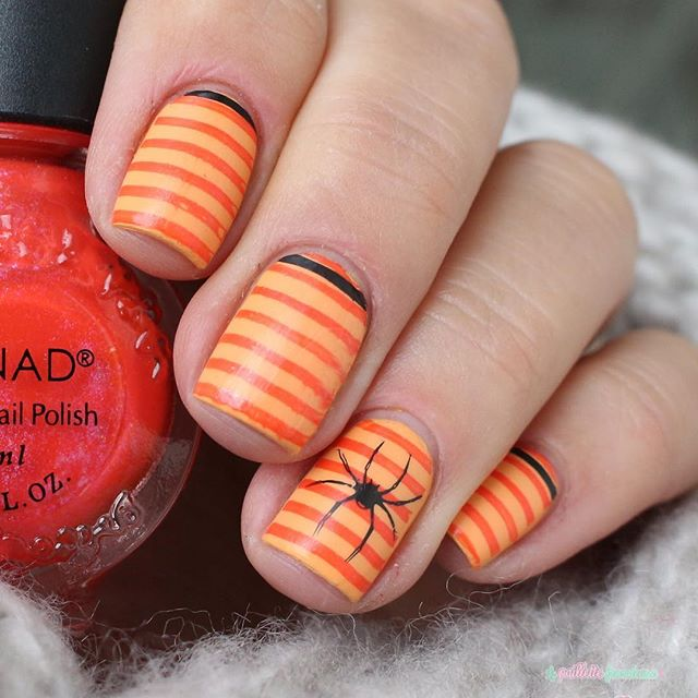 orange Halloween nails with stripes and spiders