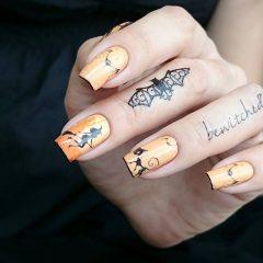 светло-оранжевый маникюр с ведьмами и татуировкой на пальцах