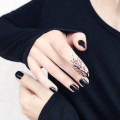 черный маникюр и черная татуировка дерево на пальце