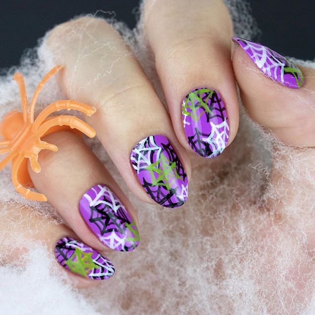 white purple and green spider web on nails