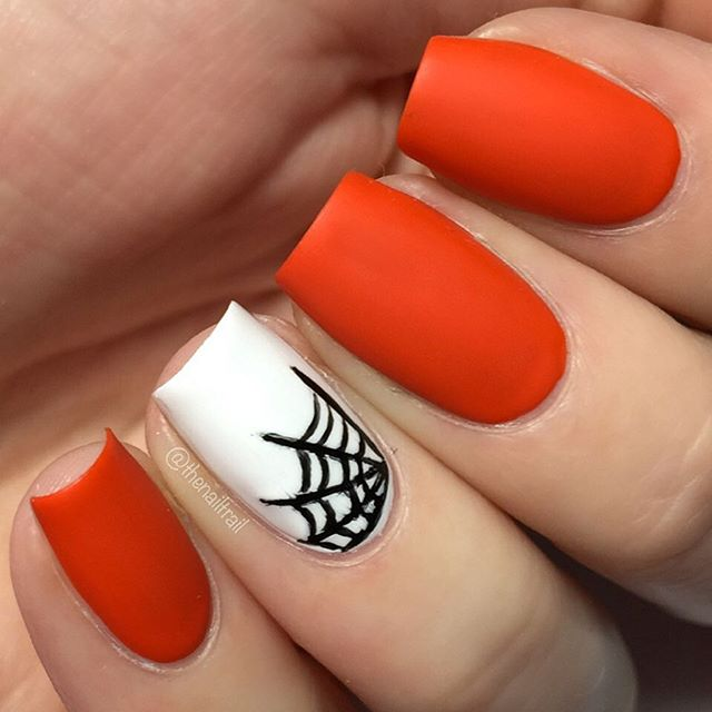 red manicure with accent white spider web nail