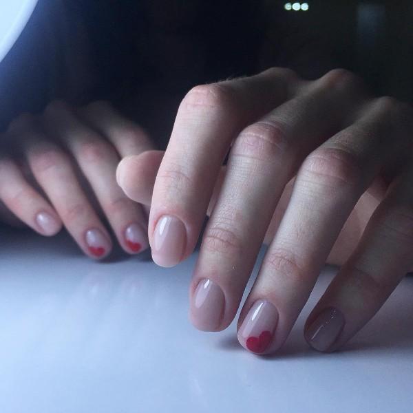 телесный прозрачный маникюр с красными сердцами в уголках ногтей